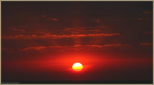 огромное солнце на закате. солнечные лучи